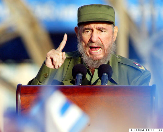 Cuban President Fidel Castro gestures as people wave flags during a speech before a demonstration Friday, May14, 2004, in front of the buiding of the US Interests Section in Havana, Cuba. The rally was organized to protest against US policy in Cuba. (AP Photo/Jose Goitia)
